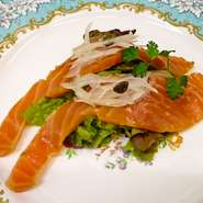ノルウェー産のサーモンを、こだわりのフランス産岩塩を使用して一日マリネしています。桜のチップでスモークした上品な香りと、サーモンのとろける、なめらかな食感がたまらない当店自慢の逸品です。