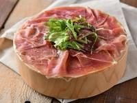 丸太の上に敷き詰められた、熟成生ハム「ハモンセラーノ」。鮮やかなピンク色でさっぱりとした味わいと柔らかな食感が特徴!