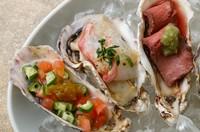 ニンニクで香りをつけたオイルに牡蠣を入れてワイン蒸しにしています。
