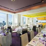 フランス人デザイナー イマド・ラムニー氏デザインの大胆な色使いのダイニングが大人のパーティを演出。皇居側に二方向に広がる大きな窓からは明るい光が差し込み、東京の絶景が映る開放的なダイニング。 シックで都会的な雰囲気のインテリアはふたりらしいコーディネートで自由に彩って。 着席30~80名、立食は最大130名と少人数の食事会から大人数のパーティまで対応が可能。
