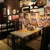 レトロな雰囲気のポスターが貼られた、落ち着きのあるテーブル席