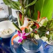 沖縄県産の野菜を自家製ソースで食べるバーニャカウダです。ソースは醤油ベースに大葉が入ったあっさりした味わい。沖縄らしく月桃で飾った華やかな一品です。