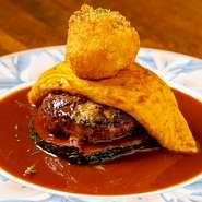 お店で包丁を使って、肉の食感が残る粗挽きミンチにした牛肉と国産ポークのハンバーグステーキ。季節の野菜を敷き、オムレツとポテトコロッケを乗せた高さのある、ボリューミーな一品です。