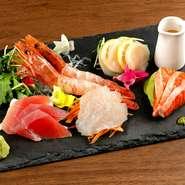 魚の卸業者から直接卸される新鮮な魚を刺身で味わえる魅惑の逸品。盛り付けの土台には、魚介と相性の良い野菜が使われおり、添えられたドレッシングをつければサラダとして楽しめます。