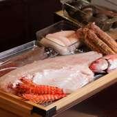 ねた箱に入った新鮮な魚介類