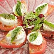 イタリア直送の濃厚でクリーミーなモッツァレラチーズとトマトとバジルのハーモニー! 定番の前菜です。