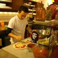 ナポリの港町で創業90年の歴史を誇る老舗レストラン「マリーノ」で修業をしたピザ職人であるオーナーの盛本さん。素朴でシンプルな味わいのナポリ料理を気軽に味わってもらえればと西区草津でお店を開きました。ナポリ風ピッツァはもとより、ナポリ定番のお菓子やババなど庶民の味にこだわりメニューを提供しています。