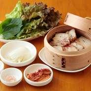 蒸し煮にした豚肉を香味野菜と一緒に食べます。白キムチ、赤キムチ、サンチュなど野菜がたくさん摂れます。