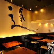モノトーンを基調とした空間に、有名書道家の直筆のダイナミックなアートが描かれた店内。