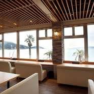 玄界灘に面した【活魚茶屋ざうお本店】。大きくとられた窓からは明るい光が差し込み、開放感あふれる空間になっています。冬は牡蠣小屋、夏はバーベキューが楽しめる点も魅力のひとつ。
