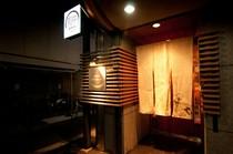 入口はバーのような大人の雰囲気。小さな看板と暖簾が目印