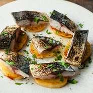 熱々のじゃがいもの上に、炙ってからマリネした鯖をのせた人気メニューです。肉厚の鯖は味がしっかりとしているので、白ワインはもちろん薄めの赤ワインに合わせるのもおすすめです。