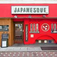 一際目を引く真っ赤な壁が【JAPANESQUE】の目印。1階のカウンターも赤をアクセントに、木肌のぬくもりがあたたかみのある雰囲気を醸し出しています。おしゃれな雰囲気の中、思い思いのスタイルで過ごせるお店です。