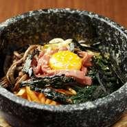 加熱済のユッケにこだわりのナムル4種や野菜類、生卵も乗った『石焼ビビンバ』は大人気メニューです。