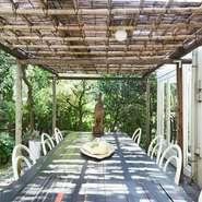 庭のグリーンが気持ちいいテラス席。テーブルの中央には野菜が天日干しされています。