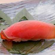 メバチ、キハダ、本マグロなど、旬の沖縄産の生マグロをお湯にくぐらせ「霜降り」にし、旨みを閉じ込めます。昆布だし、かつおだし、しょうゆ、酒、みりんで柵のまま漬けに。薄切りにした赤身の美しさにも大満足。