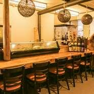 重厚感のある一枚板のカウンター。生簀の活魚や獲れたての鮮魚を肴に、日本酒もすすみます。流木や照明が温かみを演出する粋な空間は大人のカップルにピッタリ。1人飲みでも居心地良く過ごせるお店です。