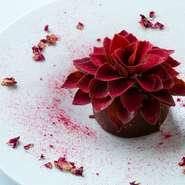 バラが美しく開花する様をデセールにした『バラのショコラ』。グラスショコラのなかにフランボワーズのソースを閉じ込め、花びらに見立てたチョコレートを一枚一枚丁寧に添えました。
