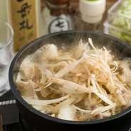 """牛鍋発祥の地""""横浜""""らしく、直径15cmの鉄鍋を使用して一人前ずつ出される濱モツ鍋。食肉店も運営しており、その店頭で55年前から販売しているモツ焼きのタレをベースにした味は、風味豊かなすき焼き風の甘さです。"""