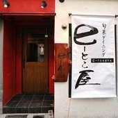 白い垂れ幕と赤い壁が目を引く店構え