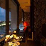 バリから取寄せたインテリアで彩られた店内は大人のくつろぎ空間。窓から公園と「アラハビーチ」が見えるカップルシートがおすすめです。ランプの優しい灯りに包まれてくつろいだひとときをお過ごしください。