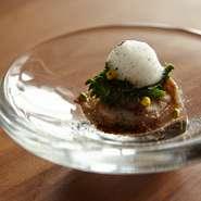 白ワインで蒸し、出す際に炭火で表面を焼いた旬の蛤。蒸した時に出るハマグリのスープと生ハムを一緒に炊いて、それを泡状のソースに。菊芋のピュレと、菜の花とともに。