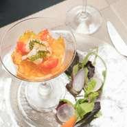 旬の野菜をムースに仕立て、サフラン風味のコンソメジュレと魚介類のマリネが添えられています。野菜本来の味を心ゆくまで楽しめるメニューです。  ※コース料理の一例です
