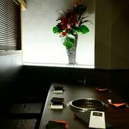 店内は、黒、ダークブラウン、ベージュを基調とした落ち着いたカラーでまとめられ、寛げる雰囲気です。花の飾りやテーブルセットなどもシックにまとめ、大人の空間を壊さないよう、工夫が凝らされています。