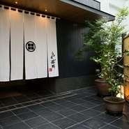 黒塀を模したエントランスは、ビルの3階にあるとは思えないほど瀟洒。真っ白な暖簾も美しく、藤田の家紋と名が眩しく映ります。店内には、カウンターのほか、テーブルや個室もありますが、どの席もゆったりと配置。