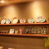 壁一面に作家の作品が並ぶ、シックな店内に華を添える明るい色調