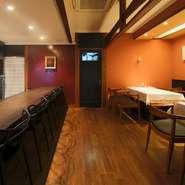 梁が印象的な店内は、カウンター席の壁はヨーロッパ風の紅、テーブル席の壁は日本の伝統的な朱色に仕上げ、和洋折衷の妙を演出。器も、フランス製の皿、有田焼や美濃焼などを用い、和洋の彩りを添えています。