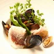 お魚料理は、毎日の仕入れによってメニューが変わるため、日替わりでさまざまなお料理が楽しめる。新鮮なお魚の良さを引き立てるように、美味しくなる調理方法を考える。写真は『天然明石鯛のシャンパン蒸し』。