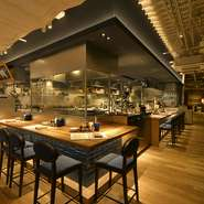 ナチュラルな木の質感と天井の鉄骨が違和感なく調和する店内。広々とした空間は開放感にあふれ、細部にまでこだわった内装が目を引きます。カウンター席では、熟成肉を丁寧に切り分ける料理人の技が見られます。