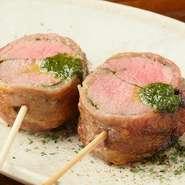 """羊肉が苦手な人も""""また食べたくなる""""と、評判の『仔羊のバジルソース』。クサミのない上質な仔羊肉を、豚肉で巻いて串焼きでいただきます。しっかりとした肉の旨味を堪能できる至福のひと串。"""