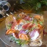入口でお出迎えするイタリアパルマ産原木生ハムを切り出した贅沢ガレット。自家製バルサミコソースとともに素材の味をお楽しみください。