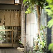 門をくぐるとアプローチの小さな庭が出迎え、柔らかな明かりが店の入り口まで導いてくれます。大切な人と時を過ごしたくなる、隠れ家のような心ときめく空間が待っています。