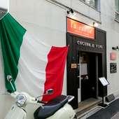 無機質なコンクリート壁に掲げられた、イタリア国旗が目印