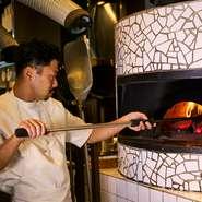 窯はシェフのつくりたいピッツアの製法に合わせて日本の職人に造ってもらい、タイルは自分たちで貼ったのだそう。ピッツアだけでなく、強く火入れしたい場合や、薪の香りをつけたい時などにも使われます。