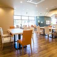 オレンジと白のイスが配され、ウッディなフローリングとベージュを基調とした内装は、アットホームでホッとできる雰囲気。シックなライティングによる演出の効果もあり、都内のカフェのように洗練されています。
