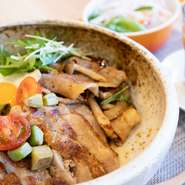 ごろっとチキンと豚生姜焼き、目玉焼き、サラダがたっぷりのったお得な丼。スープ付き、ごはん大盛り無料