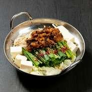 自家製のニンニク味噌に一晩漬けこんだ牛もつを使用した鍋。下味のしみ込んだもつは、ふわふわした食感を楽しめます。ニラ・ごぼう・キャベツ・もやしと、野菜もたっぷり。2名から注文可能で、写真は2~3人前です。