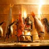 オレンジ色の炭火が灯る落ち着いた空間で味わう、囲炉裏割烹料理