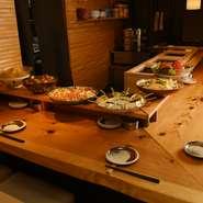 季節によって替わるおばんざいが、ずらっと並ぶカウンター席はほっこりとした温かい空間。大皿に美しく盛り付けられた料理の一皿一皿はどれも食欲をそそります。料理に合わせて酒を選ぶ、会話も弾む楽しい時間です。
