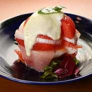 丁寧に下ごしらえされた新鮮トマトと生ハムが美しく盛られた『丸ごとトマトのサラダ ~豆富ドレッシング~』。オリジナルの豆富ドレッシングを添えた、繊細な一皿に仕上がっています。