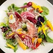 たっぷりの季節の野菜を盛り込んだ自慢のサラダ。野菜ベースでビネガーが効いた、さっぱり風味のドレッシングが野菜の味わいを引き立てます。生ハムはイタリア産で、滋味に満ちた塩気が野菜と絶妙にマッチ。