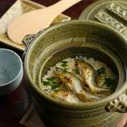 春は山菜、夏は鮎(写真)、秋はきのこなど、その季節ごとの一番ご飯に合う山の食材を用いた「釜炊きご飯」または「雑炊」。ご飯は、白山麓の粒の大きい「ヒメの舞」他、地元米が使用されています。