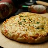 店内で伸ばしたピザ生地は、じっくり焼くと独特のふっくらした食感に。トロトロのチーズにカリッとしたベーコンの塩っ気がベストマッチ。近隣の飲食店からも注文がくるという人気の一品です。