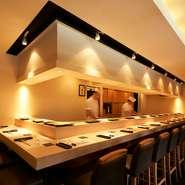 装飾を極限まで控え、モダンなデザインに仕上げた上質空間。直線的を活かしたカウンターは特等席です。目の前で職人による、握りたての鮨は格別です。デートや夫婦での食事、仕事後の乾杯にも最適です。