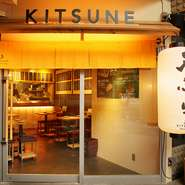 KITSUNEの看板とおおきな提灯が目印、黄色ののれんをくぐれば、オープンキッチンが目に飛び込みます。ショーケースには新鮮なネタが並べられ、目の前で揚げる天ぷらのライブ感が楽しめます。