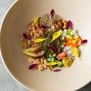 """美しさ・味・食感とも未体験の""""食""""を楽しめる一皿。自家発酵の茶葉を中心に、旬野菜・果物・ナッツ・桜エビなど10種ほどの食材を組み合わせ。季節のソースを絡めると、多彩&重層感のある驚きの美味しさに。"""